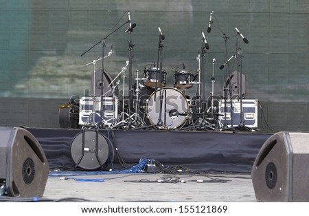 Drums set, powerful speakers, amplifiers and equipment on stage - stock photo