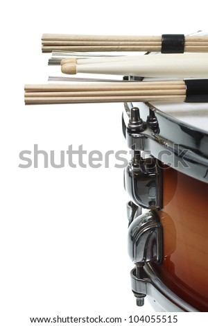 Drumsticks and unplugged sticks resting on a cherry sunburst colored snare drum, shown only a part of its side with the metal rim- isolated on white - stock photo