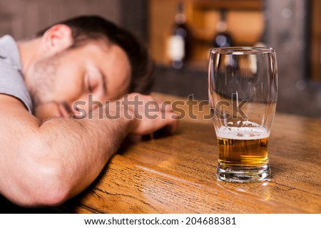 Drunk again. Drunk male customer leaning at the bar counter and sleeping while glass with beer standing near him  - stock photo