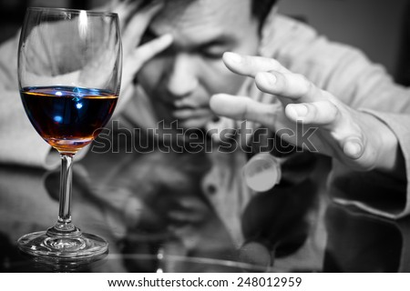 Drunk and lonely asian man & wine glass and wine, whiskey bottle / focus to glass - stock photo