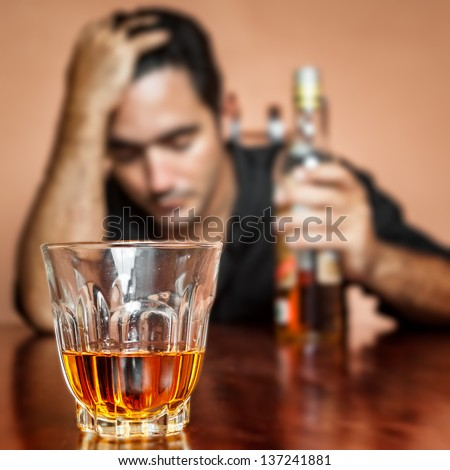 Drunk and lonely latin man holding a rum or whiskey bottle (image focused on his drink) - stock photo