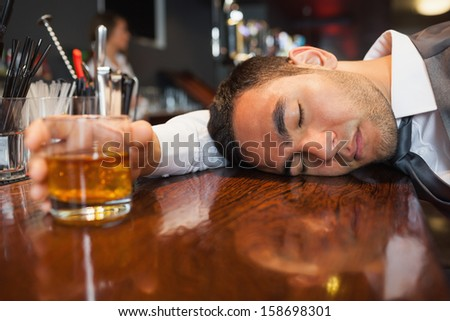 Drunk and unconscious businessman lying on a counter in a classy bar - stock photo
