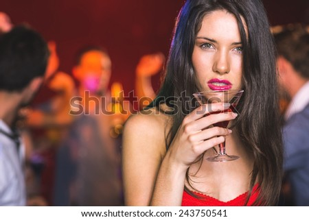 Drunk brunette looking at camera at the nightclub - stock photo