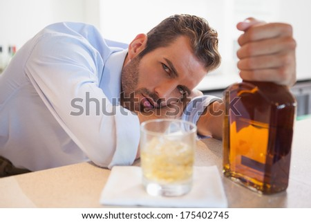 Drunk businessman clutching whiskey bottle looking at camera at the local bar