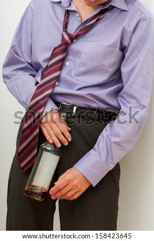Drunk businessman with whisky trying to stand up