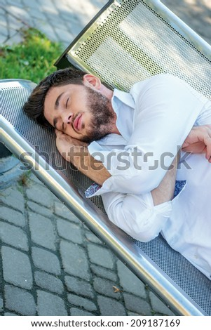 Drunk businessman. Young businessman sleeping on a bench after a hard day - stock photo