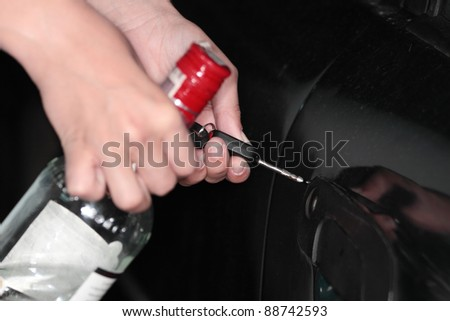 Drunk driver concept - girl holding vodka bottle, trying to open car doors - stock photo