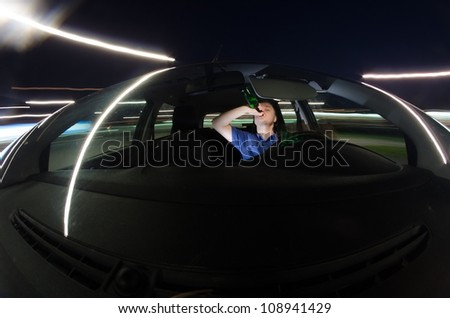 Drunk driver drinking alcohol while driving a car at night - stock photo