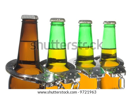 Drunk driving concept - bottled beer and handcuffs. - stock photo