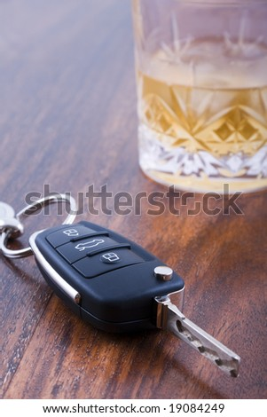 Drunk driving concept - car keys on table with glass of whiskey - stock photo
