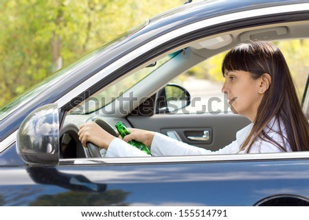 Drunk female driver with impaired ability staring blearily at her dashboard while gripping the wheel tightly and holding onto her bottle of alcohol - stock photo
