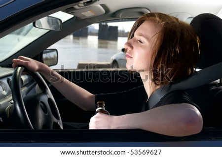 Drunk female driving car with whiskey bottle in her hand