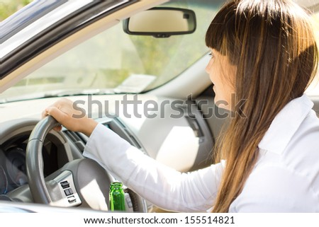 Drunk female motorist grinning as she drives with one hand on the steering wheel and the other holding a bottle of alcohol - stock photo