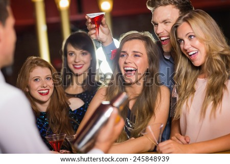 Drunk friends watching barman making cocktail at the nightclub - stock photo