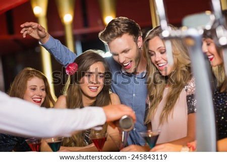 Drunk friends watching barman pouring cocktail at the nightclub - stock photo