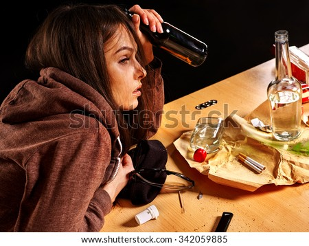 Drunk girl holding bottle of alcohol. Soccial issue alcoholism. Side view. - stock photo