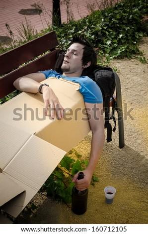 Drunk guy sleeping on a park bench, a concept - stock photo