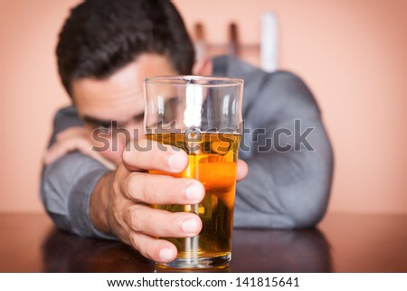 Drunk hispanic man holding a glass of beer - stock photo