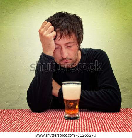 Drunk man at the pub table with a glass of beer. - stock photo