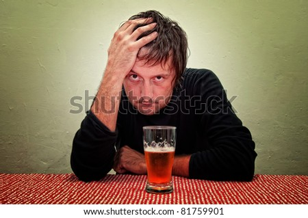 Drunk man at the pub table with a glass of cold, light beer.