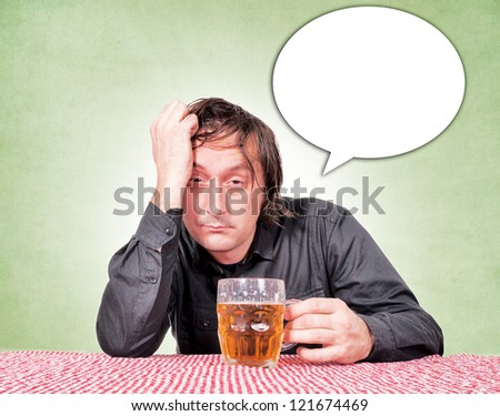 Drunk man at the pub table with a pint of beer. - stock photo