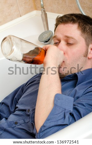 Drunk man drink alcohol lying in bath - stock photo