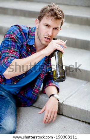 Drunk man drinking wine on the stairs and smoking cigarette - stock photo
