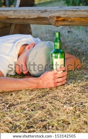 Drunk man holding a bottle of alcoholic beverage sleeping on the ground next to a bench in the park in summer - stock photo