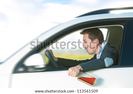 Drunk man holding bottle of whiskey in left hand. Person driving and drinking alcohol. Outdoor action with young guy inside white car. Risky travel. Bright and sunny summer day in background. - stock photo
