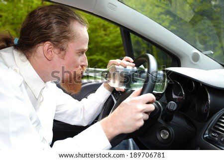 Drunk man in car with a bottle alcohol - stock photo