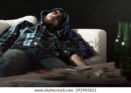Drunk man in sunglasses sleeping on couch - stock photo