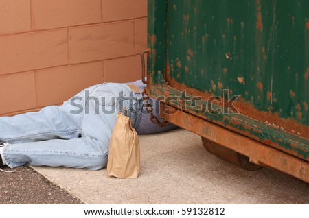 drunk man passed out behind a dumpster - stock photo