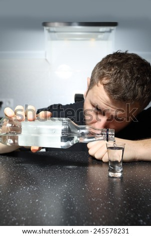 drunk man pours a glass of vodka - stock photo