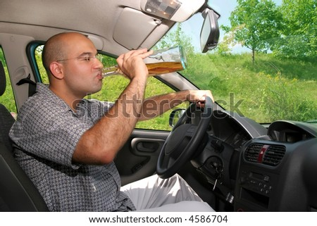 Drunk man sitting in drivers sit and drinking from a bottle - stock photo
