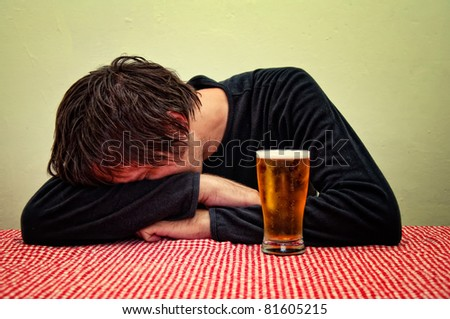 Drunk man sleeping at the pub table with a glass of beer.