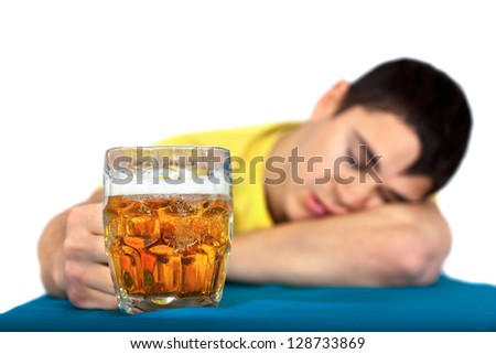 Drunk man sleeping at the pub table with a glass of cold, light beer.Isolated on white background