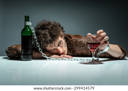 Drunk man sleeping at the table with a glass of wine / photo of youth addicted to alcohol, alcoholism concept, social problem - stock photo