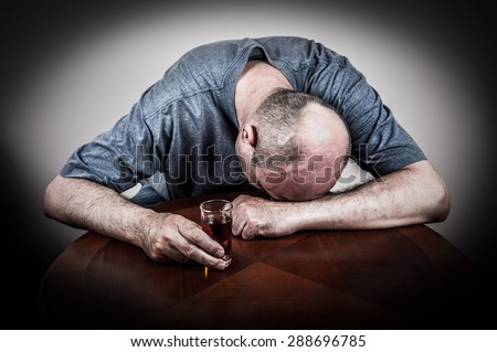 Drunk man sleeping at the table with his head on the hand and holding a glass of alcohol drink - stock photo