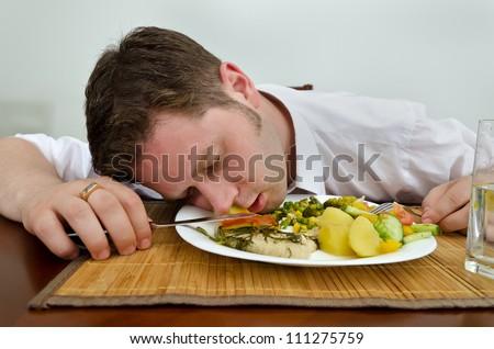 Drunk man sleeping in his dinner plate - stock photo