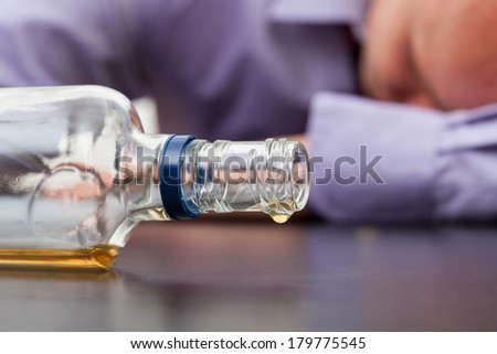 Drunk man sleeping with almost empty bottle of alcohol - stock photo