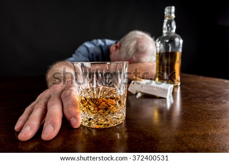 Drunk man slumped on table after alcohol abuse