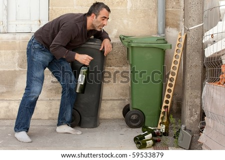 drunk man smoking cigarette and standing near trashcan - stock photo