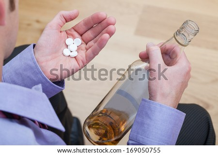 Drunk man wearing suite taking a drugs and drinking an alcohol - stock photo