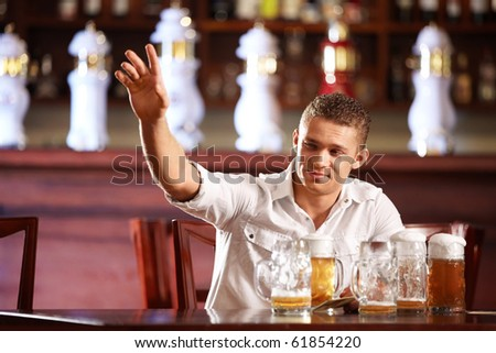 Drunk man with a beer beckons the waiter