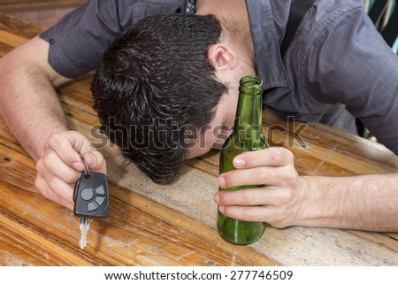 drunk man with car keys in one hand and in the other hand a bottle of beer - stock photo