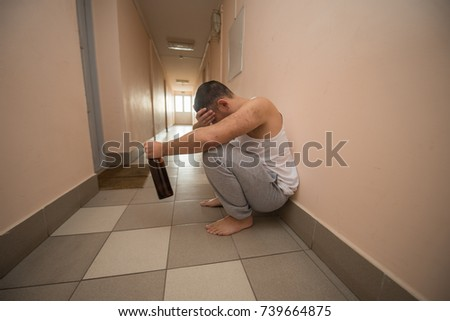 drunk sad man sits alone on the corridor with a bottle of alcohol. Harmful habits, alcoholism
