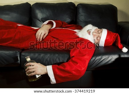 drunk Santa Claus posing with a bottle of whisky - stock photo