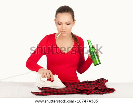Drunk smoking young woman ironing clothes and keeping bottle of beer, housework - stock photo
