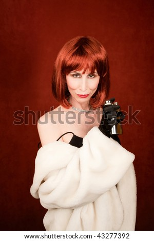 Drunk socialite with brassy red hair and flask of alcohol - stock photo