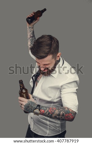 Drunk tattooed bearded man in a white shirt isolated on a grey background. - stock photo
